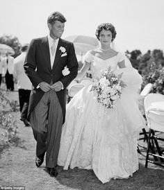 American royalty: John F. Kennedy is pictured walkingalongside his bride Jacqueline Kennedy née Bouvier at their 1953 outdoor wedding reception in Newport, Rhode Island