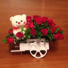 Rosas rojas en carreta con oso peluche