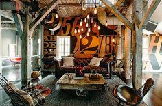 salon de style industriel aménagé avec un canapé Chesterfield en cuir marron une table basse style industriel et suspensions ampoules
