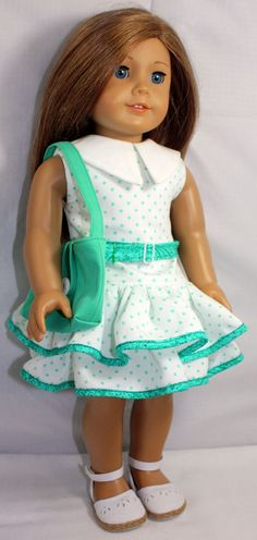 This 1930s polka dot dress is made of cotton pique and has two full ruffles with back velcro closure. The belt is removable. The purse is lined with a antique button closure. All seams are serged. This outfit fits a standard American Girl or 18 inch doll. Gift box included.    Doll and shoes not included.    Sewn with a Liberty Jane pattern.    Sewn in pet-free, smoke-free home.