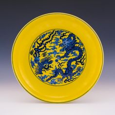 A shallow blue and yellow plate. The center design depicts a dragon and phoenix with a Flaming Pearl and multi. on Apr 2018 Yellow Plates, Chinese Art, Blue Yellow, Auction, Pottery, Design, Ceramica, Pottery Marks