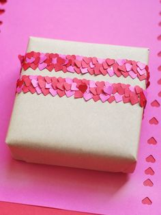 punch hearts.. add double-sided tape to your parcel, and place the confetti on the tape using tweezers