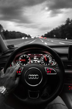Audi...in the driver's seat steering wheel interface light round metallic button multifunction hand interior sport speed highway black red