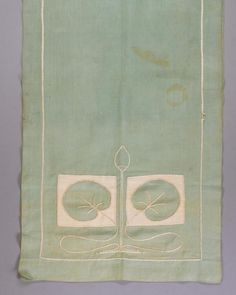 A GUSTAV STICKLEY EMBROIDERED TABLE SCARF. Long rectangular scarf embroidered in white on green linen on both ends with stylized leaves and blossom in thread and cloth. Embroidered on reverse with Stickley logo. Together with a beige linen doily with... (Sold for over $4,000.)