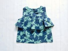 This+unique+navy+and+green+sunflower+print+blouse+has+a+ruffle+layer+just+above+the+waist+that+looks+like+a+peplum+top.+The+back+of+the…