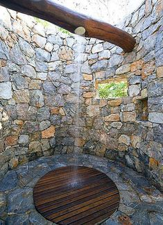 Build Naturally with Sigi Koko - An outdoor shower in stone wood...a few plants would add to the ambiance as well. (The plumbing lines are carved into the upper log,) Photo from Mandala Homes More