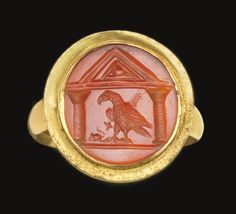 A ROMAN GOLD AND CARNELIAN FINGER RING   CIRCA 1ST CENTURY A.D.   The thin hoop rounded on the interior and exterior, expanding slightly where it merges with the broad oval bezel, set with a flat stone engraved with an eagle and a mouse within a naiskos supported on spirally-fluted columns, the eagle holding a sheaf of wheat