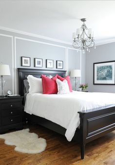 """There is one window in this room - it goes into a corner and is a little awkward. We treated it with white 3 1/2"""" plantation shutters and layered them with custom black out drapery with grommets hung on a black rod. The drapery fabric is a white matelasse. The idea is that the room be completely neutral so that the accent colour (in this case a bright pink) can be changed to suit the client's mood."""