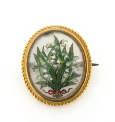 A reverse painted carved crystal brooch, depicting lily of the valley in a gold frame. 2cm high.