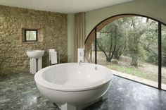 What's better than sinking into a soaking tub that measures six feet across? Doing so while enjoying views of Tuscan vineyards and oak forest. The cast resin tub is only one of the luxury details at Casa Escaiole, one of 28 restored and reconstructed farmhouses for whole or fractional ownership at Castello di Casole. The bathroom also includes a native stone veneer wall with a reclaimed brick .