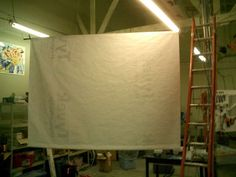 Tyvek Projector Screen (9x7) or make out of white 12 gauge vinyl shower curtain, stretched over a light wooden frame. Works like a champ. Cheap too (under $15US to build).