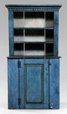 Blue-painted step back cupboard,  dentil-molded cornice, paneled door opening to shelved interior, rich blue-painted surface, some period elements, 79-1/4 x 41-1/2 x 19-1/2 in.    Reassembled incorporating some period elements, chips and losses to painted surface, other wear, abrasions, minor repairs and losses.