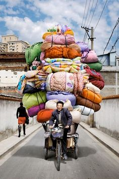 Vietnam is known for its cargo bikes, but these delivery men and women in China make the pedalers of Saigon look like pansies. Photographer Alain Delorme became fascinated with the bike haulers of China, especially how their raw humanness contrasts with the sterility of the countrys booming skyscrapers and yet their towering forms are similar.