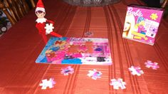 Elf on a Shelf puts together a puzzle
