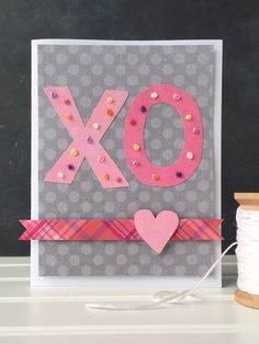 Make a pretty homemade Valentine's Day card with a few simple cutouts and a pattern of hand-stitched knots. Cut out a rectangle of patterned paper slightly smaller than the front of your blank card. Glue and stitch your embellishments to the patterned paper, then glue the finished piece to the front of the card to hide the backside of the stitching.