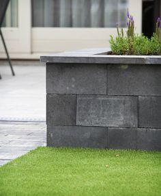 Deze buitenruimte laat zien hoe u verschillende materialen, structuren en texturen kunt combineren. We gebruikten kunstgras, keramische tegels, straatwerk en split, en werkten de tuin af met kleurrijke beplanting.