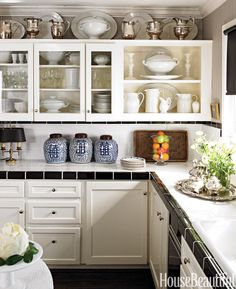 """The kitchen is a good size, but small by Dallas standards — only about 16 x 16,"" designer Craig Schumacher says of this Texas kitchen in the house he shares with partner Philip Kirk. They avoided an extensive kitchen remodel by painting existing cabinets Benjamin Moore Brilliant White and installing inexpensive black and white tile on counters and backsplashes. An extensive ironstone collection overflows from shelves to walls. Vintage jurors' chairs were picked up at assorted flea markets…"