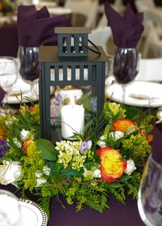 Detail of table centerpieces; Lanterns surrounded by flowers.