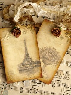 A pretty pair of antiqued Paris inspired tags accented with a touch of glitter and petite paper rosettes.