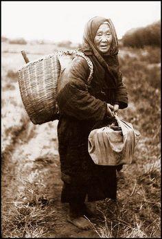 Barefoot in winter - An elderly farmer's wife on her way to the fields, ca 1915-23.