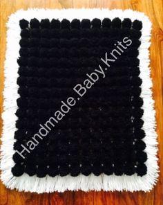 Black pom pom blanket with white base and tassles.
