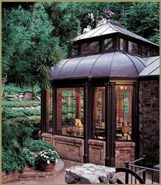 Conservatory with curved copper roof used as informal dining space off the kitchen