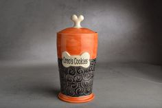 """MADE TO ORDER (ALLOW 12 WEEKS PRIOR TO SHIPPING)we have temporarily extended our production time due to a high volume custom ordersTime to give your pet a super cool treat jar. Or use it for your own special treats.This treat jar will be wheel thrown by Scott Reed and slip-trail decorated and glazed by Angi Pogue-Reed.Shown with optional personalization for Oreo.Hand painted in a transparent black and orange.9"""" tall x 4-1/8"""" wide x 3-3/4"""" opening..."""