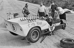 Franz Weis works on the left front of Roger Penske's Chaparral at Nassau, December 1964. Also recognized are Jim and Sandy Hall. This car suffered suspension failure during the race, and this is a post-race photo taken out on the race course, where the car was repaired. Penske took over Sharp's race leading Chaparral during the mandatory pit stop, and they shared the win. Note that the spoiler is inserted into a slot in the duck tail, located by fasteners. Eric della Faille photo.