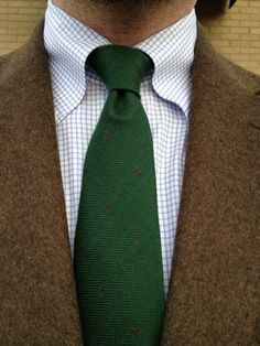 Brown tweed jacket, white shirt with light blue check, green tie