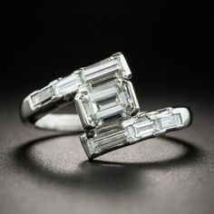 The sleek diagonal geometric design of this mid-century dazzler, hand fabricated in gleaming platinum and starring a bright white and shining emerald-cut diamond weighing .70 carat, distinguishes this striking vintage engagement ring. The scintillating stone is elegantly presented between rows of baguette diamonds set end-to-end for a gorgeous gleaming effect. 1.45 carats total diamond weight, currently ring size 6 1/2.