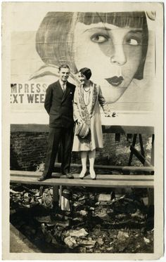 Lionel Barrymore and his wife Irene Fenwick in front of a Louise Brooks billboard, 1920s
