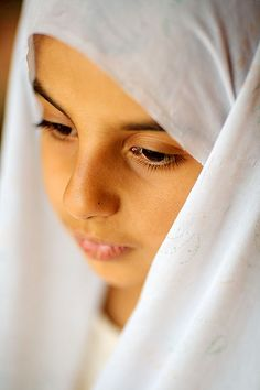 A young Iranian girl wears a white hijab in the style of a chador. She is looking away from the camera down to the ground. Photo taken on August 2007 in Kaj, Chaharmahal and Bakhtiari Province, Iran.