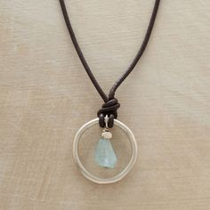"""LIFE'S CIRCLE NECKLACE--An aquamarine nugget swings inside an organic circle of recycled sterling, brushed to a satin finish and suspended on leather cords. Silver extension clasp. Handmade in USA exclusively for Sundance. Size and shape of stone will vary. 17"""" to 19""""L."""