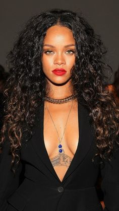 Rihanna's lion mane hair is long, curly and voluminous –– the perfect compliment to her striking red lipstick.