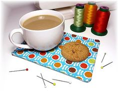 A small display using a nice coffee mug or fancy tea cup, and perhaps some ITH toy cookies (or real ones!) to show how to use this tiny placemat. (it also works as AG sized doll placemats)  I picked this design because just the one design has several variations. Change the fabric and stippling, and you've got an entirely new style to offer customers many choices.   4x4 folks, check this board for coasters which can be made with your machines.