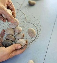 Filling wire heart with grey pebbles for the Wire and stone heart DIY home decor craft project