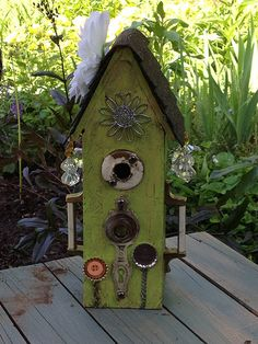 Birdhouse made out of upcycled and repurposed material now yard art.