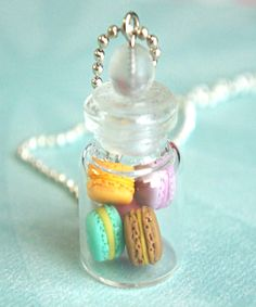 this necklace features a miniature jar of handmade french macarons sculpted from polymer clay. the glass jar measures about 2.5 cm tall and is securely attached to a silver tone ball chain necklace th