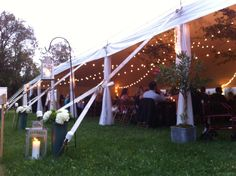 Wedding tent illuminated with candle lanterns and bistro lights