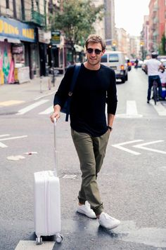 How Coveteur Co-founder Jake Rosenberg Spends His Day: Black Long Sleeve Tee Shirt and Beige Pants by Kit and Ace, Blue Leather Backpack, Sunglasses, White Sneakers, White Luggage | coveteur.com