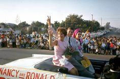 California Republican gubernatorial candidate Ronald Reagan and his wife Nancy wave to spectators as they ride in back of convertible car outside while on the campaign trail in 1966.