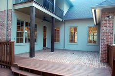 French Courtyard with Brick Pavers and Guest Bedroom overlook Porch look down to Deck. Best in MS Award Winner by AAA Homes of MS, LLC