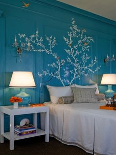 Turquoise wood-paneled walls overlaid with a hand-painted branch and bird mural. The branches overlap onto the acrylic headboard.