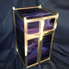 300 cubic inch urn with solid brass framing and cross, polished to a high glossy finish. The glass is a Dark Purple/White.  $439.95 www.stainedglassurns.com