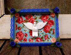 Charmoso mini oratório com divino em madeira, forrado com tecido florido e enfeitado com pérolas, renda e flores de cetim.    Acompanha ganchinho e fita para pendurar em parede.  Peça única!