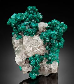 DIOPTASE Renéville Mine, Renéville, Kindanba District, Pool Department, Republic of Congo  Here a large and intergrown mass of Dioptase crystals  are partially embedded in colorless Calcite of subhedral form.