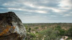 A pan and linear timelapse moving past granitic rock boulders revealing the distant landscape at sunrise with clouds moving. Bouldering, Stock Footage, Sunrise, Past, Trees, Clouds, Rock, Landscape, Water