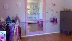 Need: Large Mirror, pole that is flat on one side, 2 triangle shelf brackets, can of primer and pink spray paint, hooks to hang on either side (I used cast iron princess crown hooks from Amazon)    Spend a few extra bucks to find a large mirror with a frame to simplify the project (I got this one for $50 at the Kirlands).  Be sure to do a quick sanding and use a primer on the mirror and pole before spraypainting.  To organize all the dress up clothes spray painted an old quilt stand pink.
