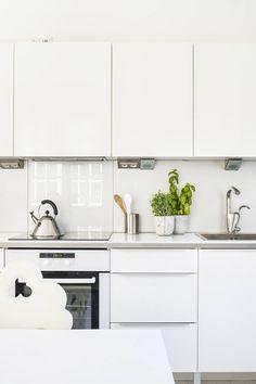 Korkeakiiltoiset keittiön kaapit ovat Domus-keittiöistä. Työtasojen reunaan on asennettu alumiinilistat. Kaapistojen välitilassa on lasilevyt.