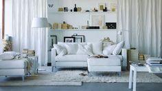 """Ein helles Wohnzimmer mit KARLSTAD 3er-Sofa + KARLSTAD Kissen mit Bezug """"Blekinge"""" weiß + vielen Textilien wie KARLSTAD RITVA Gardinenschals mit Raffhaltern weiß, Plaids URSULA gebleicht + GURLI in Weiß/Beige + den langflorigen Teppichen HAMPEN in Weiß + ÅDUM in Elfenbeinweiß"""